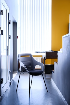 Zwarte stoel in gang van appartement, echte foto met exemplaarruimte op de witte muur
