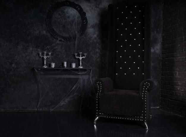 Zwarte stoel met hoge rugleuning en met spinnenweb bedekte kandelaars in angstaanjagende halloween-spookhuisomgeving