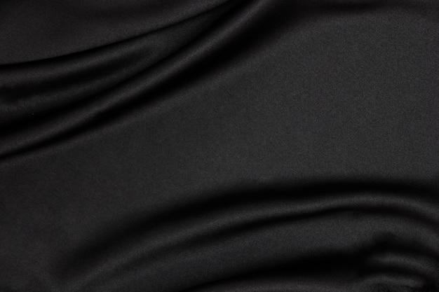 Zwarte stof textuur achtergrond. soepele elegante zwarte zijde kan als trouwachtergrond worden gebruikt.