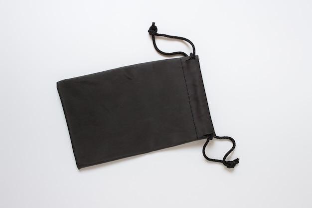 Zwarte stoffen verpakkingstas sjabloon mockup op wit oppervlak.