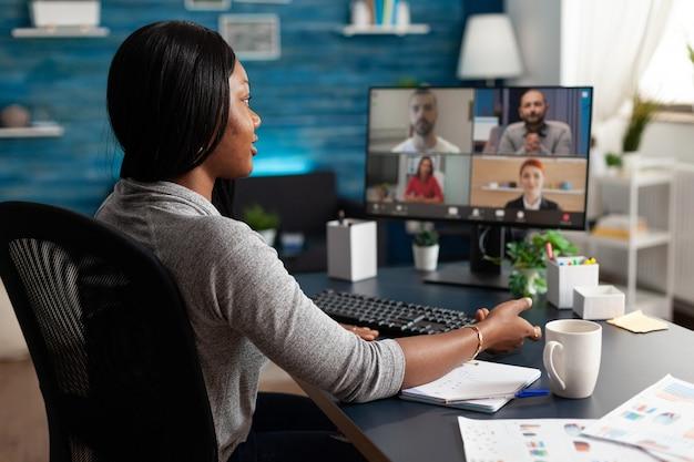 Zwarte student in gesprek met universiteitsteam tijdens online videocall-vergaderingsconferentie