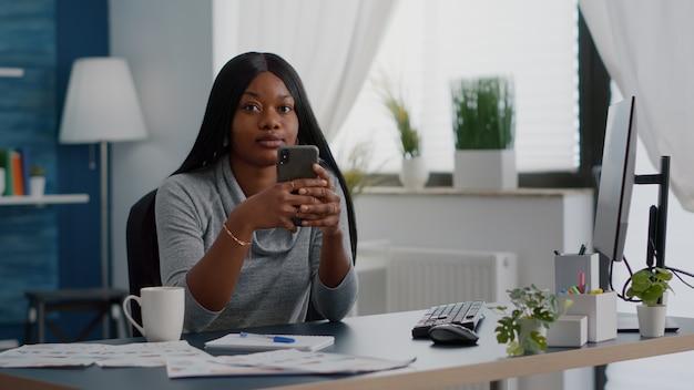 Zwarte student met telefoon in handen en chat met mensen die communicatie-informatie doorbladeren