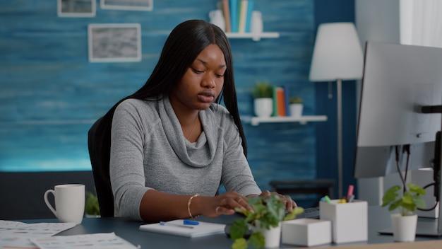 Zwarte student zit aan het bureau en schrijft schoolhuiswerk op notebook tijdens online cursussen