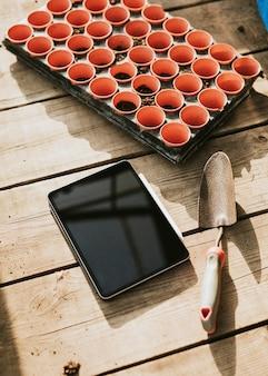 Zwarte tablet door een tuintroffel op een houten tafel