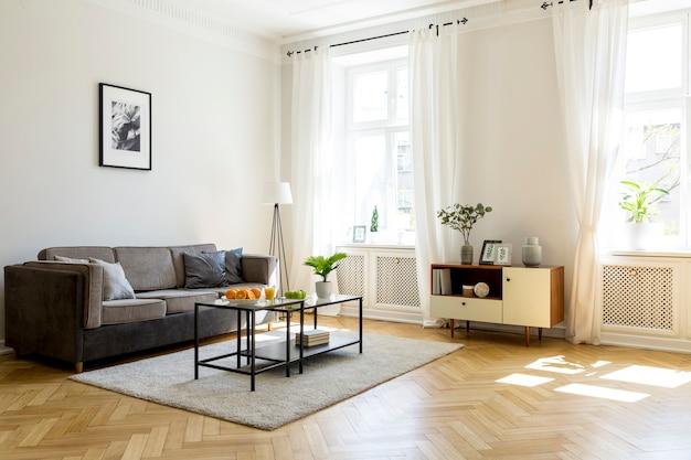 Zwarte tafel op tapijt in ruime woonkamer interieur met poster boven grijze bank. echte foto