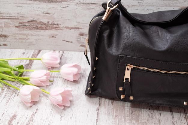 Zwarte tas op een houten achtergrond, roze tulpen. modieus concept.
