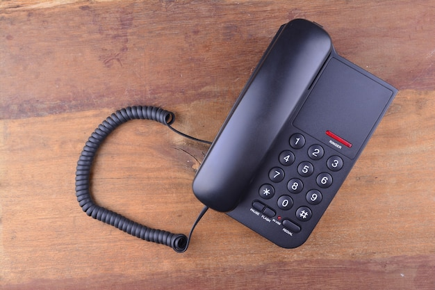 Zwarte telefoon op houten tafel Premium Foto