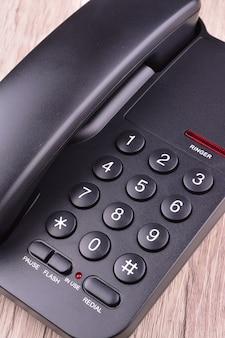 Zwarte telefoon op houten tafel