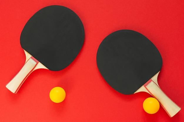 Zwarte tennis pingpongrackets en oranje ballen geïsoleerd op een rode achtergrond