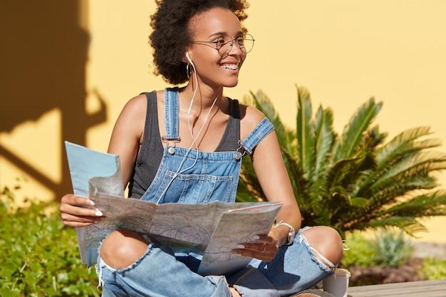 Zwarte tevreden afro-amerikaanse vrouwelijke reiziger gebruikt bestemmingskaart voor het zoeken naar interessante plaatsen, zoekt naar bezienswaardigheden op onbekende plaatsen, geniet van radio-uitzendingen in oortelefoons, vormt buiten