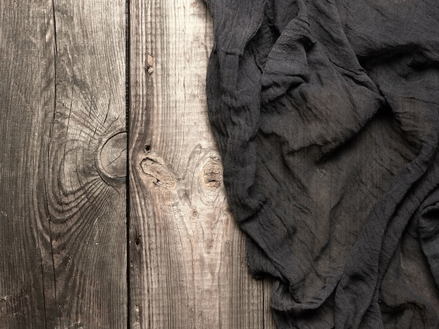 Zwarte textiel keukendoek gevouwen op een grijze houten tafel