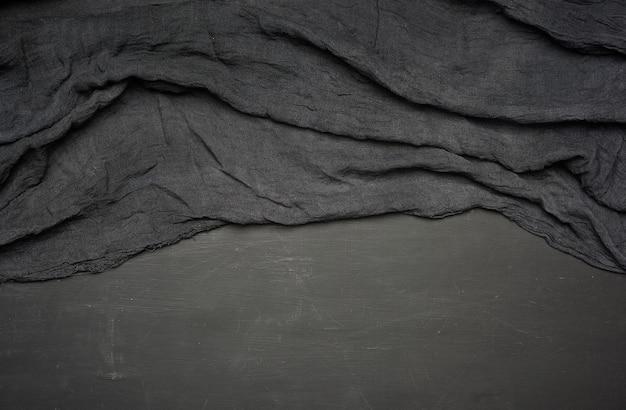 Zwarte textiel keukenhanddoek gevouwen op een zwarte houten tafel