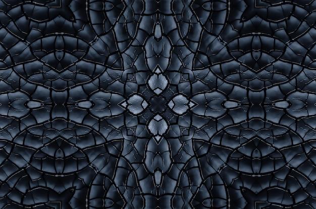 Zwarte textuur van verbrand hout symmetrische achtergrond. verbrande bord close-up. gevolgen van een brand, het caleidoscoopeffect