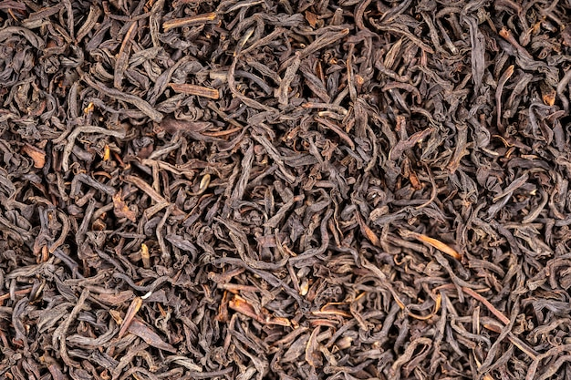 Zwarte thee bladeren achtergrond. abstracte voedsel texturen. close-up, bovenaanzicht