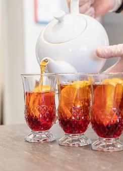 Zwarte thee die uit een theepot in een glas wordt gegoten