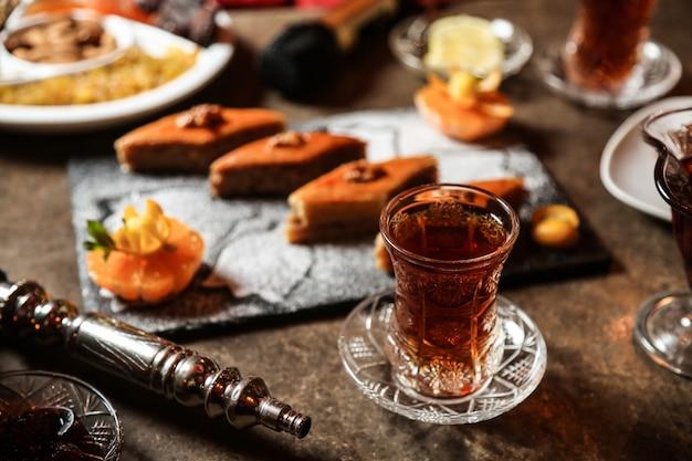 Zwarte thee in armudu glas met diverse zoetigheden op tafel