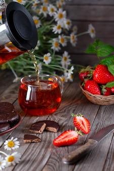 Zwarte thee in een glazen beker op een houten tafel met chocoladeschilferkoekjes en aardbeien. verticaal