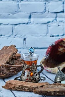 Zwarte thee in een traditionele glazen beker en koekjes op blauwe houten tafel