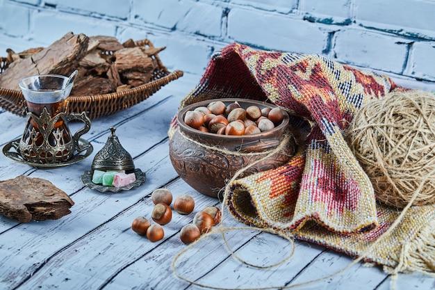 Zwarte thee in een traditionele glazen beker met snoepjes en een kom met hazelnoten op blauwe houten tafel