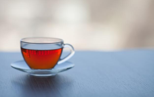 Zwarte thee in glazen beker op onscherpe achtergrond.