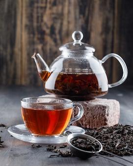 Zwarte thee in theepot en kopje met droge thee, bakstenen zijaanzicht op een houten oppervlak