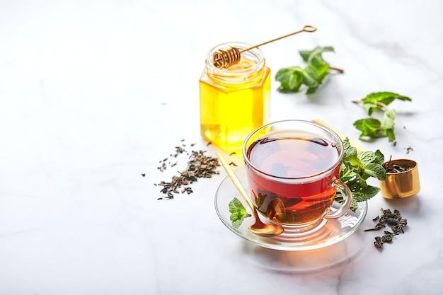 Zwarte thee in transparante glazen mok met muntblaadjes en honing kalmerende en revitaliserende thee, antistress en ontspanning