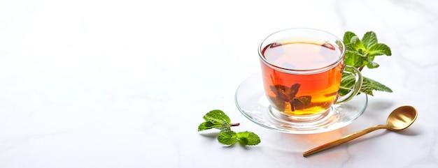 Zwarte thee in transparante glazen mok met muntblaadjes rustgevende thee antistress