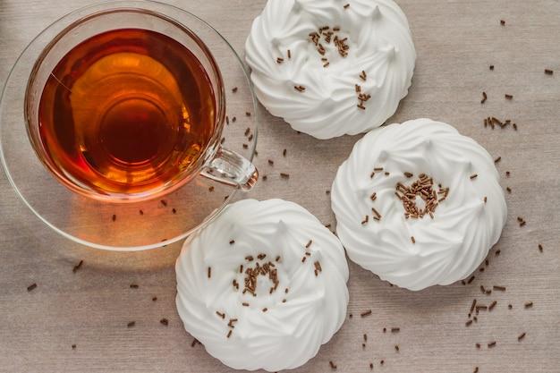 Zwarte thee in transparante kop lucht eigengemaakte schuimgebakjes dicht omhoog