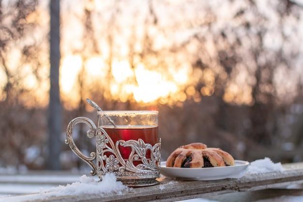 Zwarte thee in vintage beker en zelfgemaakt maanzaadbroodje