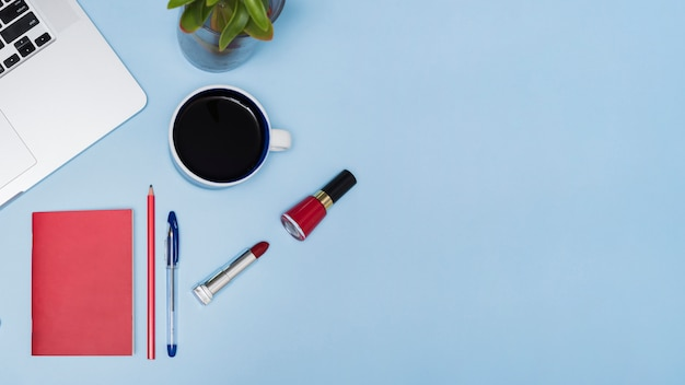 Zwarte thee; laptop; fabriek; briefpapier en lippenstift op blauwe achtergrond