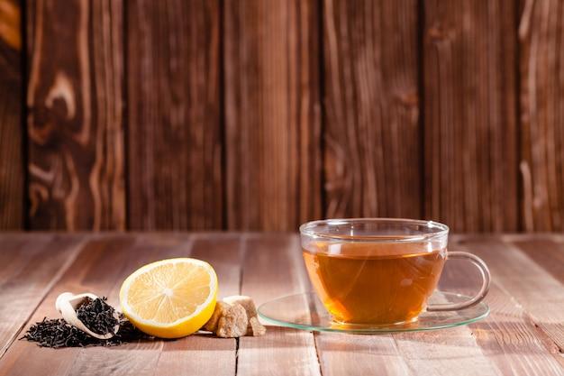 Zwarte thee met citroen en bruine suikerklontjes op de houten tafel, plaats voor tekst