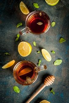 Zwarte thee met citroen en mint op donkerblauwe betonnen steen, copyspace bovenaanzicht