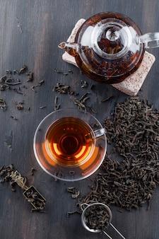 Zwarte thee met droge thee, baksteen in theepot en cup op houten oppervlak, bovenaanzicht