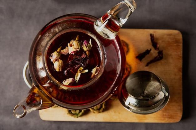 Zwarte thee met rozenbloemen in een glazen doorzichtige theepot met een kopje, mooi ontbijt