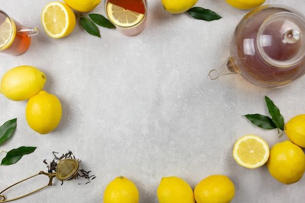 Zwarte thee met verse citroenen en bladeren op lichtgrijs betonnen oppervlak