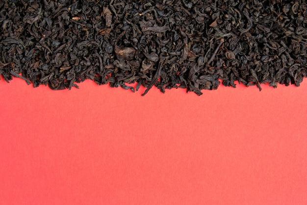 Zwarte thee op een rode achtergrond. bovenaanzicht