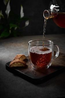 Zwarte thee wordt uit de theepot in een transparante beker gegoten met bubbels in de buurt van koekjes bij het snijden