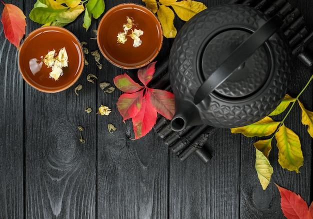 Zwarte theepot en groene thee met jasmijn in een kleikop, op zwart en houten met herfstbladeren voedsel bovenaanzicht