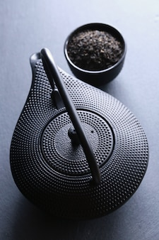Zwarte theepot erin en twee kopjes thee