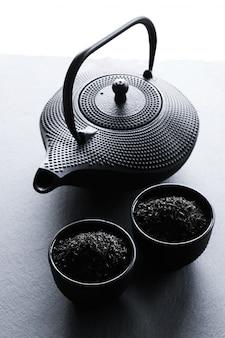 Zwarte theepot in oosterse stijl en twee kopjes thee