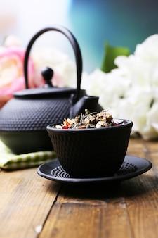 Zwarte theepot, kom en hibiscusthee op kleuren houten lijst, op lichte achtergrond