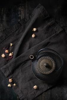 Zwarte theepot met droge rozen