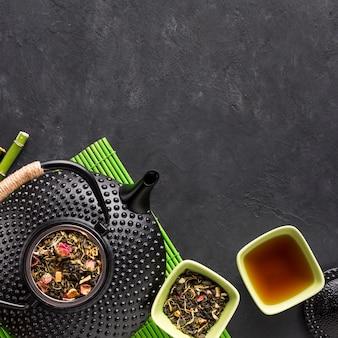 Zwarte theepot met gedroogd theekruid op de achtergrond van de leisteen