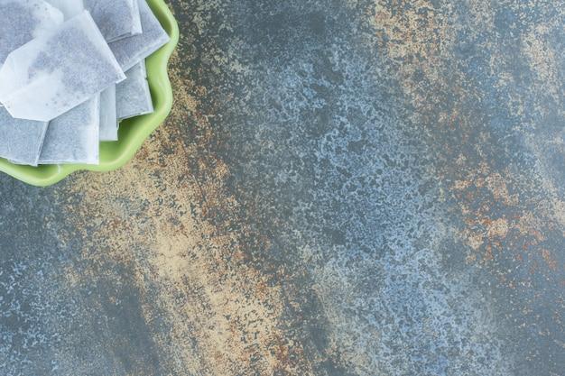 Zwarte theezakjes in groene kom op marmeren tafel.