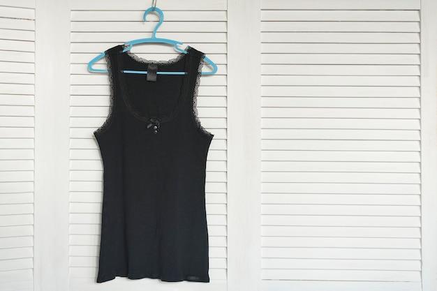 Zwarte trui op de hanger. witte luiken op de achtergrond