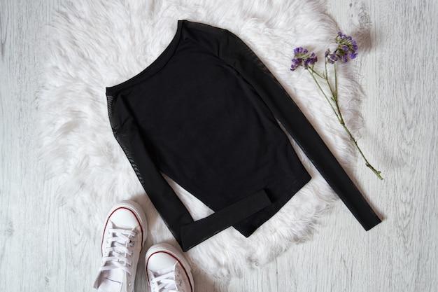 Zwarte trui op wit bont, sneakers.