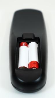 Zwarte tv-afstandsbediening met aaa-alkalinebatterijen in rood en wit op een witte achtergrond. vervanging van de batterij, reserveonderdelen. afstandsbediening batterijcompartiment close-up. verticale fotografie.