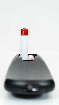 Zwarte tv-afstandsbediening met aaa-alkalinebatterijen op een witte achtergrond. vervanging van de batterij, reserveonderdelen. close-up van het batterijvak van de afstandsbediening. verticale fotografie.
