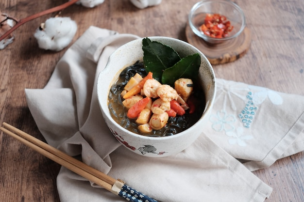 Zwarte udon met garnalen in de kom met eetstokje en stof op de houten tafel