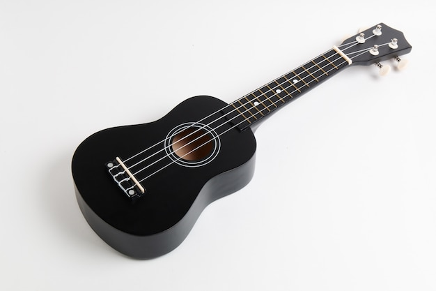 Zwarte ukulele-gitaar op wit